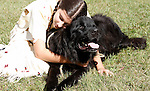 A young Native American Indian girl hugging a black dog