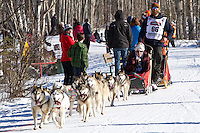 Mike Ellis and team run past spectators on the bike/ski trail during the Anchorage ceremonial start during the 2014 Iditarod race.<br /> Photo by Britt Coon/IditarodPhotos.com