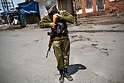 A soldier from the paramilitary force, Central Reserve Police Force (CRPF) is seen patrolling the streets on empty streets in the downtown area of Nowhatta, Srinagar, summer capital of Jammu and Kashmir, India. A 50 hour curfew was imposed on May 5th to boycott the elections on May 7, 2009. ..Kashmir went into polls on the 4th round of Indian general elections. About 26 percent polling was recorded in the Indian parliamentary elections held in Kashmir on Thursday, May 7th 2009. The poll percentage was on the higher side this year as compared to 2004 polls when 15.04 percent polling was recorded.