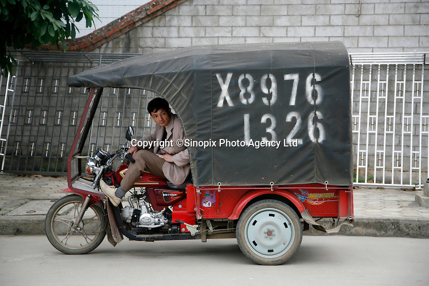 A man sits in his motor rickshaw while waiting for customers in Pingxiang, Guangxi Province, China..10 Apr 2007