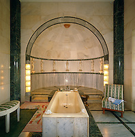 A marble-clad bath in the centre of a dramatic green and white marble bathroom with a row of statuettes lining the wall of the alcove