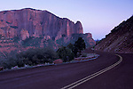 Curving road in evening light below red rock cliffs in the Kolob Canyon area, Zion National Park, Utah.