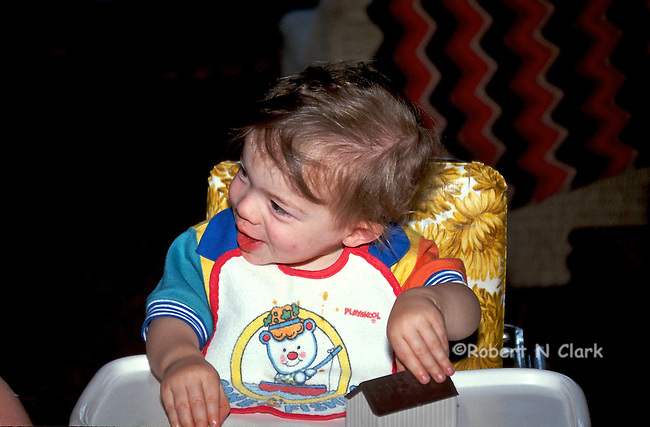 Boy in high chair smiling at someone off camera