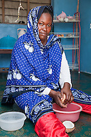 Jambiani, Zanzibar, Tanzania.  Woman Making Coconut Milk.  She wears a nose-pin in her left nostril.