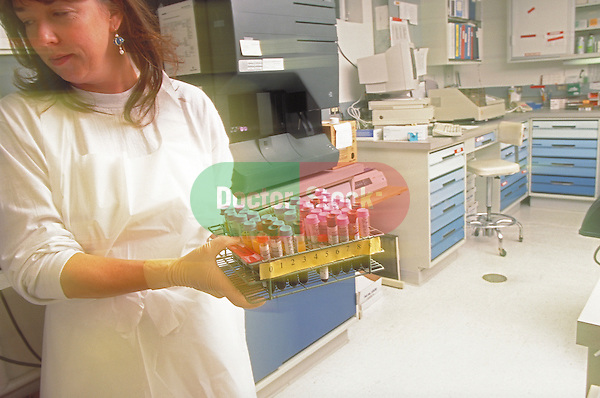 lab technician carrying rack of specimen vials in laboratory