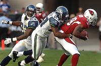 Nov. 6, 2005; Tempe, AZ, USA; Wide receiver (19) LeRon McCoy of the Arizona Cardinals is tackled by cornerbacks (23) Marcus Trufant and (27) Jordan Babineaux of the Seattle Seahawks at Sun Devil Stadium. Mandatory Credit: Mark J. Rebilas