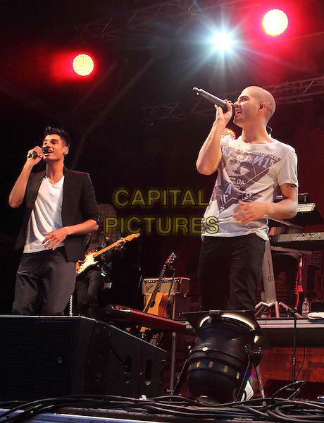 Siva Kaneswaran and Max George of The Wanted.performing at the Love Luton Festival at Popes Meadow, Luton, Bedfordshire, UK, July 6th 2012..music band group gig live on stage half length white t-shirt microphone singing jacket black .CAP/ROS.©Steve Ross/Capital Pictures