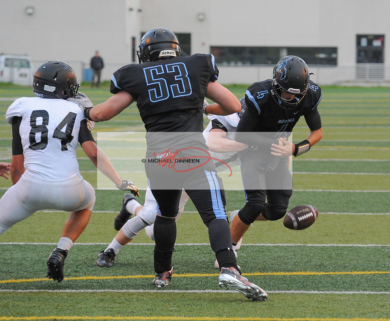 Service's Beck Stokes causes a fumble by Mustangs' quarterback Hunter Harr at Chugiak High School Friday, August 19, 2016.  Photo for the Star by Michael Dinneen