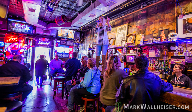 A country music singer with a British accent sings atop the bar in Tootsie's Orchid Lounge on lower Broadway in Nashville, Tennessee