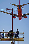 People  working on runway approach lights beneath  jet airplane landing at Los Angeles Int'l Airport LAX, California