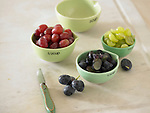 Red, black, and green grapes in small ceramic measuring cups