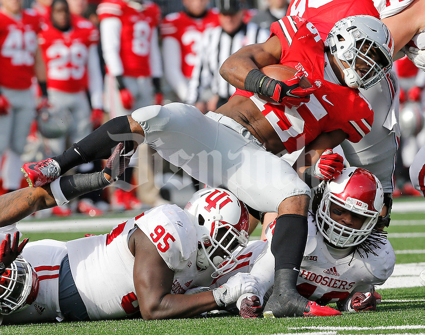 Ohio State Buckeyes running back Ezekiel Elliott (15) is tackled by Indiana Hoosiers defensive tackle Bobby Richardson (95) in the third quarter of their game at Ohio Stadium in Columbus, Ohio on November 22, 2014. (Columbus Dispatch photo by Brooke LaValley)