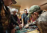 PR and Web Director for the National Wild Turkey Federation Brent Lawrence (cq, second left), OutdoorLife Editor Andrew McKean (cq, middle) and others look over a map to plan the next day's hunt in Superior, Nebraska, Wednesday, November 30, 2011. ..Photo by Matt Nager