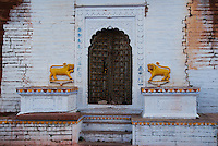 Painted lions guard a ruined place door, Rajasthan, India.