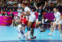 28 JUL 2012 - LONDON, GBR - Heidi Løke (NOR) of Norway (second from left in red) finds her path to goal blocked by Camille Ayglon (FRA) (left, in white) of France and her team mate Nina Kamto Njitam (FRA) (centre, in white) during their women's London 2012 Olympic Games Preliminary round handball match at The Copper Box in the Olympic Park, in Stratford, London, Great Britain .(PHOTO (C) 2012 NIGEL FARROW)