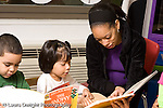 Education preschool 4 year olds female teacher looking at book and reading to girl, boy looking at his own book nearby horizontal