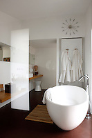 In the main bathroom the elegant oval bath is made of polished concrete and the washstand and bench along the wall have been built from warm chestnut wood