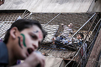 A Syrian youths chant anti government slogans, one by microphone and another one from a balcony, during a demostration after friday prayers in the Bustan Al Qasr district of Aleppo, Syria.