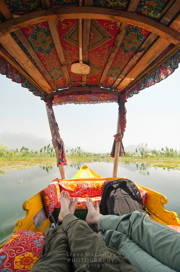 Point of view photograph of tourists feet propped up on seat of brightly decorated shikara, Dal Lake, Srinagar, Kashmir, India.