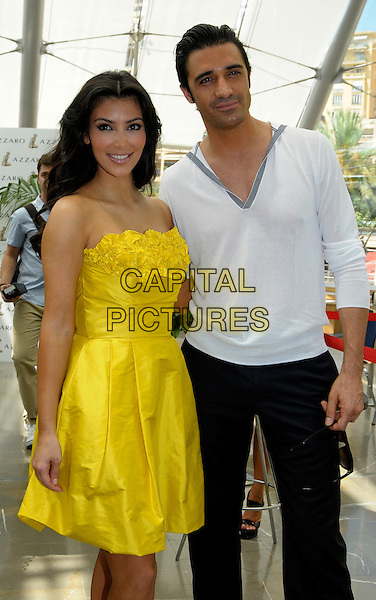 KIM KARDASHIAN & GILLES MARINI.Photocall during the 49th Monte Carlo Television Festival at the Grimaldi Forum, Monte-Carlo, Monaco..June 10th, 2009 .half 3/4 length white top trousers v-neck yellow strapless ruffled ruffles dress.CAP/RD.©Richard Dean/Capital Pictures.