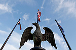 An eagle figure at with blue skies and flags in the background