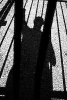 Shadow of man behind bars