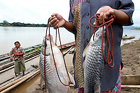 The wife of a fisherman holds two fish she's going to sell at the market in Chiang Khan, Thailande-2010