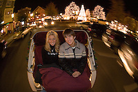 A young couple riding in a carriage keep warm during the annual Christmas tree lighting event at Birkdale Village in Huntersville, NC. Birkdale Village combines the best of shopping, dining, apartments and entertainment venues within a 52-acre mixed-use development.