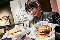 A members of staff holds a Western Bacon and Guacamole Bacon Thickburgers during the pre-opening event for the Japan's first Carl's Jr. burger restaurant located in Tokyo's Akihabara district, on March 2, 2016, Japan. The Californian fast food restaurant follows on the heels of Shake Shack in entering the Japanese market. Mitsuuroko Group Holdings Co., Ltd. has signed a franchise agreement to operate Carl's Jr. branches in Japan with the first to open to the public on March 4th. (Photo by Rodrigo Reyes Marin/AFLO)