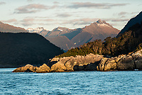 Sun sets on rocks at entry into Doubtful Sound entrance, Fiordland National Park, Southland, UNESCO World Heritage Area, New Zealand, NZ