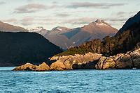 Sun sets on rocks at entry into Doubtful Sound entrance, Fiordland National Park, Southland, UNESCO World Heritage Area, New Zealand, NZ
