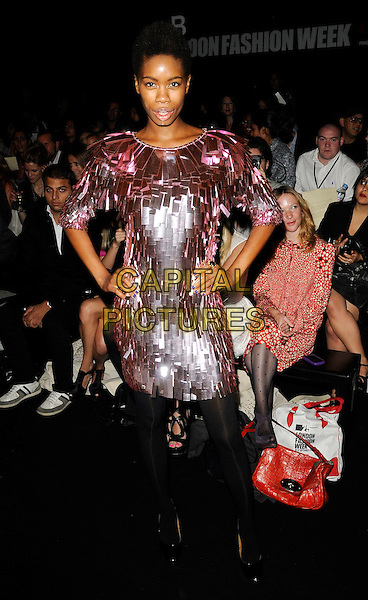 TOLULA ADEYEMI.At the Issa Show, London Fashion Week Day 3, Somerset House, London, England, UK,.September 20th 2009..full length pink shiny fringed dress hands on hips futuristic black tights tassels layered .CAP/CAN.©Can Nguyen/Capital Pictures.