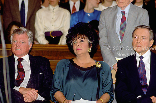 "Washington, DC -- March 6, 1990 -- United States Senator Edward M. ""Ted"" Kennedy (Democrat of Massachusetts), left, and U.S. Senator Orrin Hatch (Republican of Utah), right, attend a Capitol Hill press conference with Actress Elizabeth Taylor, center, concerning some AIDS legislation on March 6, 1990..Credit: Howard L. Sachs / CNP"