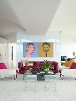 The luxurious penthouse apartment is full of edgy chic and sizzling colour. In the living room a pair of silk-screened prints by Andy Warhol hang above a 1960s Edward Wormley sofa upholstered in a Scalamandré velvet. The Louis XVI stools, circa 1780, are from Bernd Goeckler Antiques.