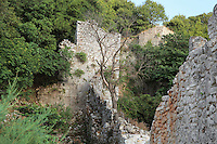 Medieval wall in ruins, Butrint, Chaonia, Albania. Butrint was founded by the Greek Chaonian tribe and was a port throughout Hellenistic and Roman times, when it was known as Buthrotum. It was ruled by the Byzantines and the Venetians and finally abandoned in the Middle Ages. The ruins at Butrint were listed as a UNESCO World Heritage Site in 1992. Picture by Manuel Cohen
