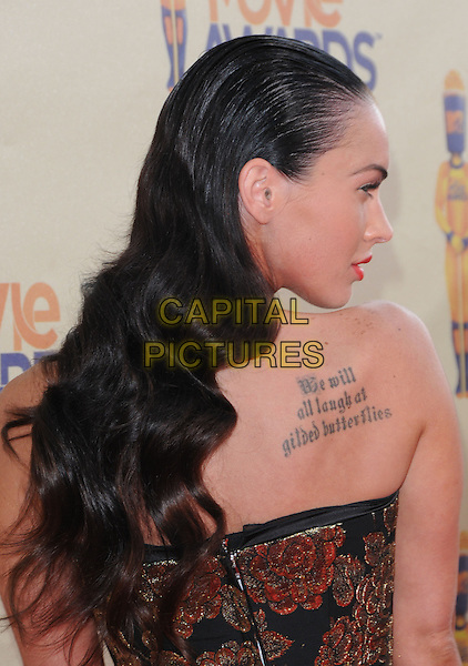 MEGAN FOX.The 2009 MTV Movie Awards held at Universal Ampitheatre  in Universal City, California, USA..May 31st, 2009  .half length black gold floral print strapless dress hair slicked combed back profile looking over shoulder profile  tattoo we will all laugh at guilded butterflies .CAP/DVS.©Debbie VanStory/Capital Pictures.