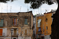 A corner of a typical small place in the old part of the town, in Bari, near the Normanno-Svevo (Swabian) castle.  The colorfulness of the old buildings is enhanced by the shutters and the curtains. There are also various street-lamps, whereas the multitude of antennas stands out on the background of the cloudy sky, with some green branches that frame the top of the photo. Digitally Improved Photo.