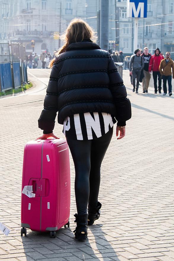 Nederland, Amsterdam, 19 maart 2015<br /> Toeriste met opvallende kleding met het woord pink en rolkoffer in de kleur pink.<br />  <br /> Foto: Michiel Wijnbergh