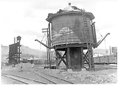 D&amp;RGW Durango water tank with two spouts but in deriorated condition and ready for replacement.  Experimental engine washer on roundhouse lead in background didn't exist for long.<br /> D&amp;RGW  Durango, CO  Taken by Payne, Andy M. - 7/10/1964