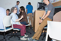 Megan Gall, of Washington, D.C., (in blue shirt with red pants, center left) speaks with Daniel McGlone, 32, of Philadelphia, Penn., during the Metric Geometry and Gerrymandering Group (MGGG) hackathon at the Data Lab in the Tisch Library at Tufts University in Medford, Massachusetts, USA, on Thurs., Aug. 10, 2017. Gall is a Social Scientist at the national Lawyers' Committee for Civil Rights Under Law. She is working on ways to routinize ecological inference statistics and then visualize that as a way to teach others what ecological inference means and does. Ecological inference is a way of using aggregate data, such as racial or ethic information, to infer what an individual might have done, in this case during a vote. McGlone, 32, is a GIS Analyst at Azavea in Philadelphia, Pennsylvania. Gall, and others investigating gerrymandering, use ecological inference as a way to identify districts that may have racially polarized voting. The hackathon is part of the first in a series of Geometry of Redistricting workshops put on by the MGGG. Academics, Geographic Information Systems (GIS) professionals, and legal professionals worked together to build tools useful in analyzing voting district data around the country.