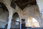 Building interior medieval church architectural feature, Inglesham, Wiltshire, England decalogue of 19th century prayer overlain on medieval paintings on chancel wall