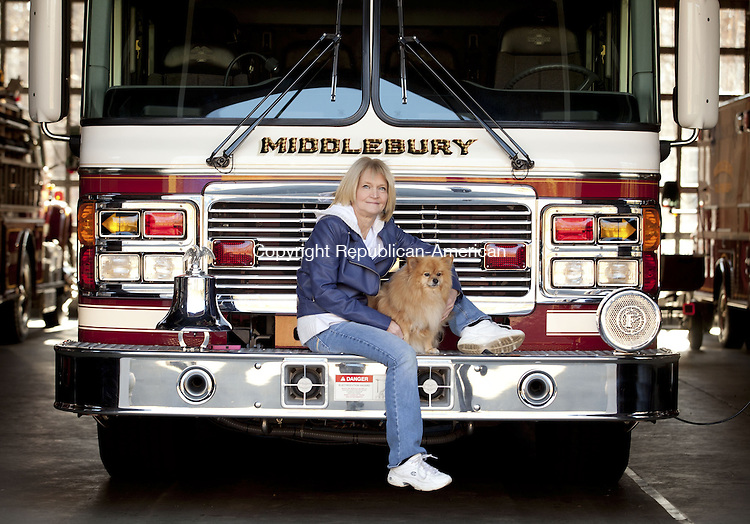 MIDDLEBURY, CT-14 November 2013-111413BF02- Beverly Dassonville poses with her 5-year old Pomeranian Chloe on a Middlebury Fire Department truck Thursday morning. Dassonville is a volunteer E.M.T. with the Middlebury Fire Department Ambulance and created a video that she entered to try to win a $500,000 dog park from the the pet food company Beneful in the Beneful Dream Dog Park Contest.  Bob Falcetti Republican-American
