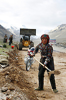 China started building a controversial 67-mile &quot;paved highway fenced with undulating guardrails&quot; to Mount Qomolangma, known in the west as Mount Everest, to help facilitate next year's Olympic Games torch relay./// A young woman works with a shovel building the road to Everest Base Camp.<br /> Tibet, China<br /> July, 2007