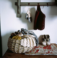 Balls of wool and knitted items are piled in a wicker basket sitting on top of a wooden table. Knitted gloves and a waistcoat hang from hooks on a peg board above.