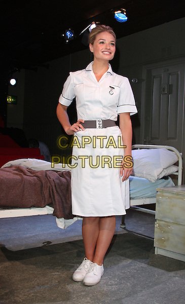 EMMA RIGBY .Emma Rigby in the theatre production 'Wolfboy' at the Trafalgar Studios, London, England, UK..July 6th, 2010.stage acting full length dress grey gray belt nurse uniform dress-up costume white bed sneakers hand on hip.CAP/ROS.©Steve Ross/Capital Pictures.