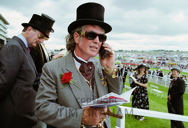 Well-dressed man with race card using early mobile phone at Epsom Racecourse on Derby Day, UK in the 1980s