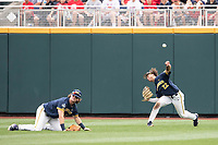 Michigan Wolverines outfielder Jordan Brewer (22) throws the ball to the infield as teammate Jesse Franklin (7) looks on during Game 6 of the NCAA College World Series against the Florida State Seminoles on June 17, 2019 at TD Ameritrade Park in Omaha, Nebraska. Michigan defeated Florida State 2-0. (Andrew Woolley/Four Seam Images)