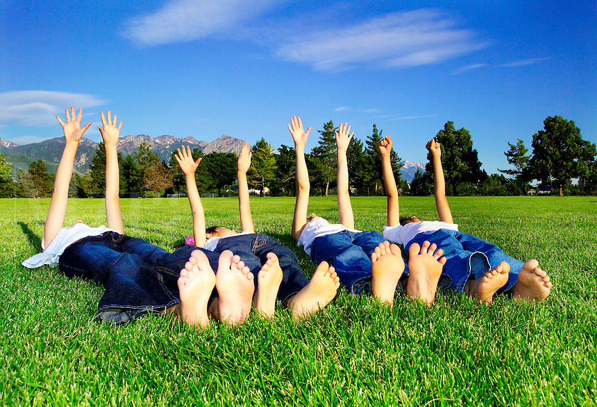 4 children laying on their backs on the grass with their arms in the air.
