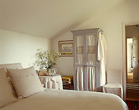 Tones of milky white and pale grey create an intimate and restful guest bedroom