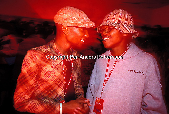 dipptee00024 .Teenager JOHANNESBURG, SOUTH AFRICA - JUNE 8: Mzee Mbele, age 19, (left) and an unidentified friend partying at a youth party for about 5.000 people at a nightclub on June 8, 2002 in Midrand north of Johannesburg, South Africa. After eight years into democracy a new black middleclass and elite is growing, and they have money to spend on houses, cars and entertainment. .©Per-Anders Pettersson/iAfrika Photos